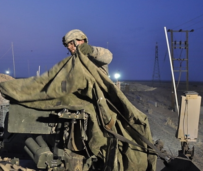 Sgt. Luke Hitchcock, 26, of Olean, N.Y., covers the .50-caliber machine gun atop his vehicle after his unit arrives in Kuwait. Fair-use photo & caption credit: Ernesto Londono-The Washington Post