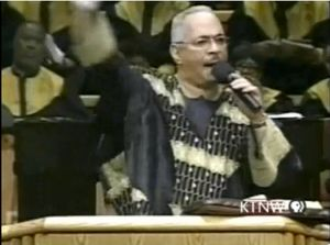 screencap of Rev. Jeremiah Wright praying for God to damn America from the pulpit of the Trinity United Church of Christ, as circulated before Obama threw Wright under the bus in 2008