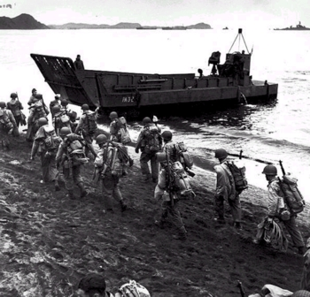 Troops march up the beach at Adak, during pre-invasion loading for the Kiska Operation, 13 August 1943. Photographed by Lt. Horace Bristol, USNR, of the Steichen photographic unit. LCM behind the soldiers is from USS Zeilin (APA-3). USS Pennsylvania (BB-38) is in the far right distance. Note the troops' packs and M1 rifles.